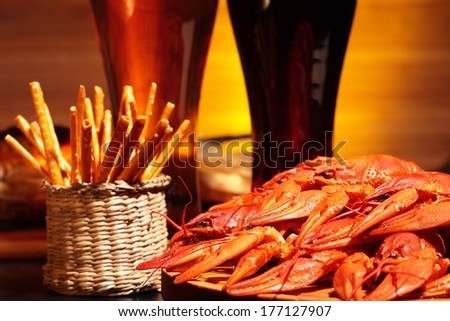 Prepared crawfish and glasses of dark and light beer - stock photo