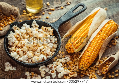 Prepared popcorn in frying pan, corn seeds in bowl and corncobs on kitchen table. Selective focus. - stock photo
