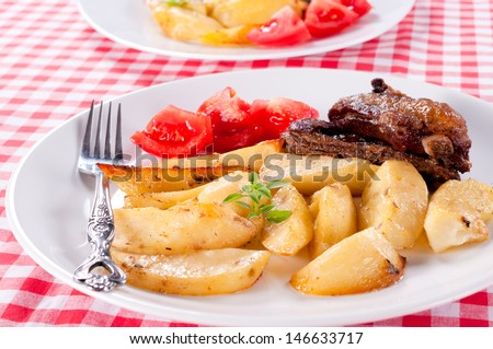 Prepared Serbian potato with pork briskets. Selective focus in the middle of potatos - stock photo