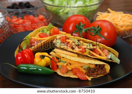 Prepared tacos with tomatoes, habanero and serrano peppers on plate.  Ingredients in background. - stock photo