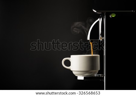 Preparing a cup of strong freshly brewed espresso coffee using a coffee machine with a side view of the beverage pouring into a white cup on a dark shadowy background - stock photo