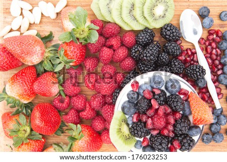 Preparing a delicious healthy berry fruit salad with assorted fresh fruit on the counter including strawberries, raspberries, blackberries, blueberries, pomegranate and kiwifruit with almonds - stock photo