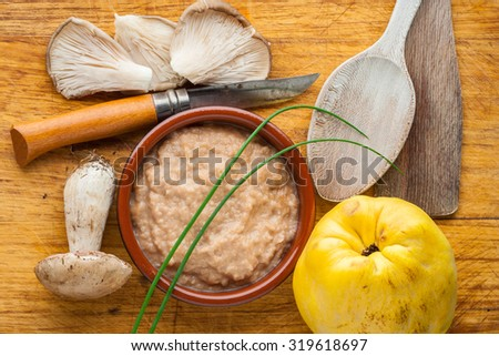 Preparing a quince sauce with mushrooms on a cutting board - stock photo