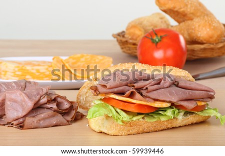 Preparing a roast beef sandwich with cheese, tomatoes, and lettuce on a bun - stock photo