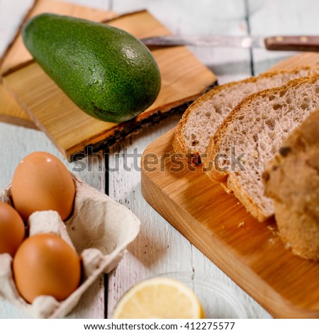 preparing a toast with eggs and avocado in the kitchen - stock photo