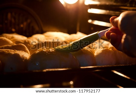 Preparing baking into the oven. Pies cover with a mixture of egg. - stock photo