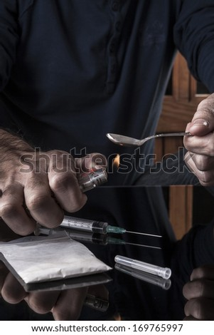 Preparing drugs on teaspoon a lighter on dark background with reflection - stock photo