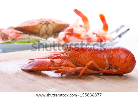 Preparing dungeness crab, red lobster and shrimps in the kitchen on the cutting board - stock photo