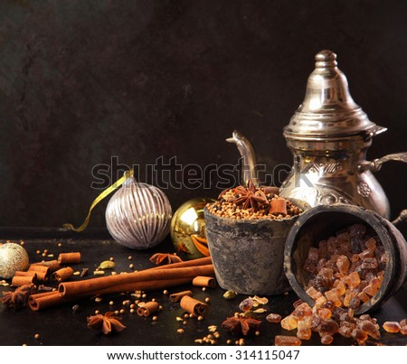 Preparing festive spicy tea for Christmas with aromatic spices including stick cinnamon , star anise and caramelized sugar with decorative Xmas baubles, a sliver teapot and copyspace - stock photo