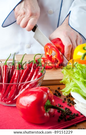 Preparing food - chef cutting a red bell pepper - stock photo