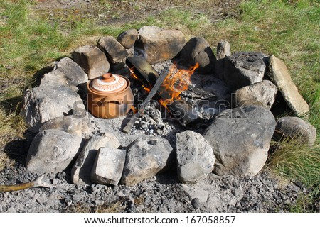 Preparing food in a traditional Bulgarian pot on campfire. - stock photo