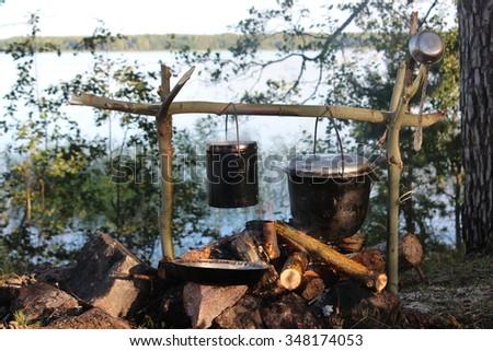 Preparing food on campfire.  - stock photo