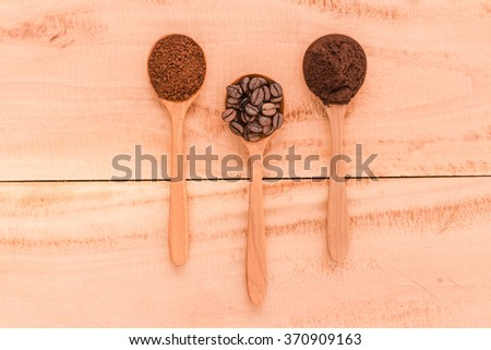 Preparing fresh roast coffee beans to brew with an overhead view of four different varieties of beans with their corresponding ground powder in small wood spoon on a weathered driftwood background - stock photo