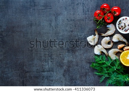 Preparing fresh seafood background with shrimp, tomatoes, fresh herbs and spices on dark vintage table, top view, space for text, border. - stock photo