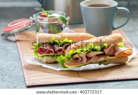 Preparing from delicious ham and fresh baguette sandwich on a sheet of paper with cup of tea - stock photo