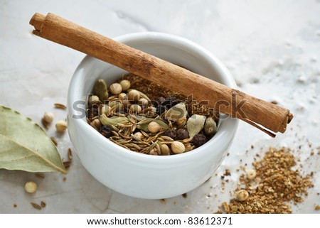 Preparing Garam Masala in a mortar made from cinnamon, pepper, cumin, coriander, bay leaf and cardamom. - stock photo
