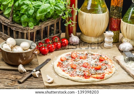 Preparing homemade pizza with fresh ingredients - stock photo