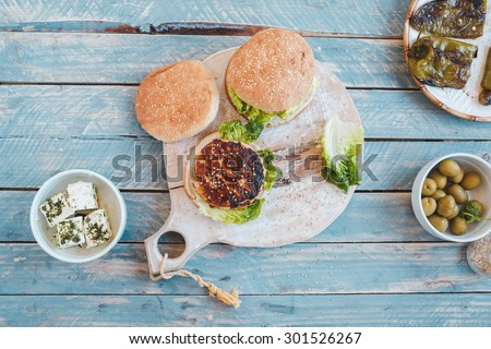 Preparing homemade two hamburgers with chicken and cheese over on a rustic cutting board from above on a blue wooden surface with olive and marinade cheese and fried pepper. Rustic style .  - stock photo
