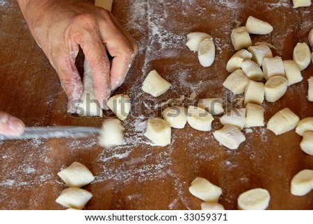 "Preparing italian ""gnocchi"" (potatoes dumpling): cutting the dough. Typical Italian food,  homemade. - stock photo"