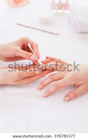 Preparing nails for manicure. Close-up of beautician cleaning nails of female customer - stock photo