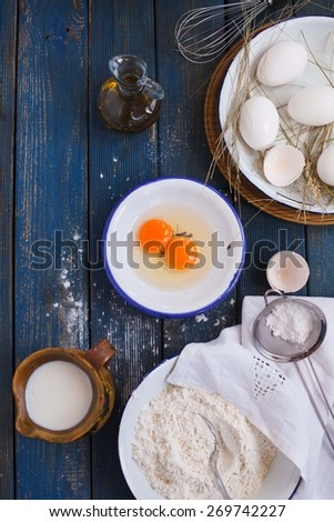 Preparing of pancakes. Baking background with eggs, flour and pottery pitcher milk, bottle oil olive. Top view. Rustic style. - stock photo