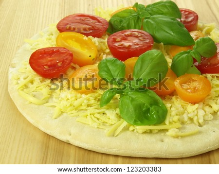 Preparing pizza with cheese and halves of tomatoes - stock photo