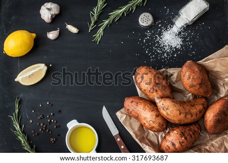 Preparing rosemary roasted sweet potatoes with olive oil, lemon, salt, pepper and garlic - kitchen scenery from above. Black chalkboard as background. Layout with free text space. - stock photo