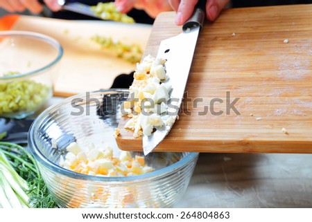 Preparing russian traditional salad Olivier, chopping boiled eggs - stock photo