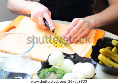 Preparing russian traditional salad Olivier, chopping pickles - stock photo