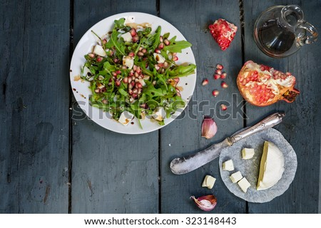 preparing salad with arugula, feta cheese, pomegranate, garlic and balsamic dressing served on a white plate on a rustic wooden table, view from above, copy space in the dark gray wood - stock photo
