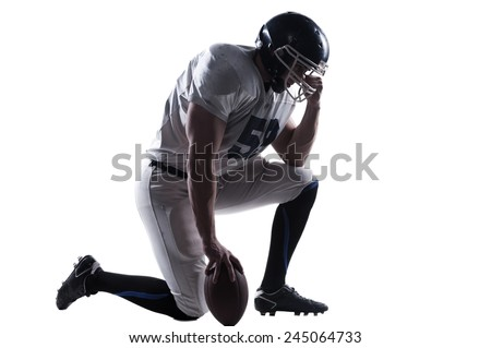 Preparing to big game. Side view of American football player holding hand on helmet while standing on knee against white background  - stock photo