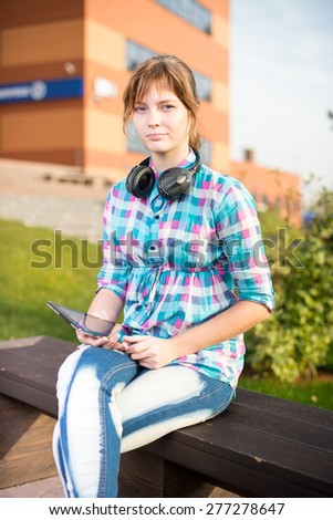 Preparing to exams outdoors. Beautiful young female student writing or reading something from note pad.  Woman sitting on bench in city park. - stock photo