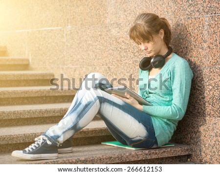 Preparing to exams outdoors. Headphones music. Beautiful young female student writing or reading something from note pad. Woman sitting on stairs in city park. - stock photo