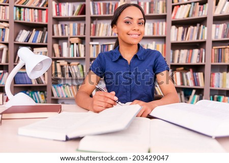 Preparing to her final exams. Confident young black woman looking at camera and smiling while sitting at the library desk - stock photo