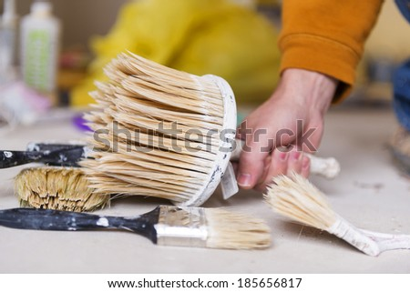 Preparing to paint the wall. Detail of man's hand painting the walls of new home. - stock photo