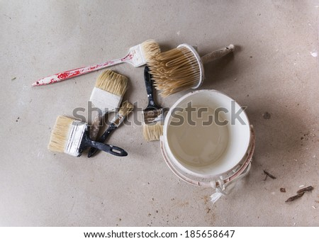 Preparing to paint the wall. Detail of paintbrush and bucket of color on the floor. - stock photo