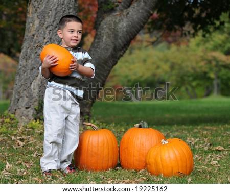 Preschool boy confidently holding a small pumpkin he's chosen for Halloween.  Shallow DOF with focus on boy's eyes. - stock photo