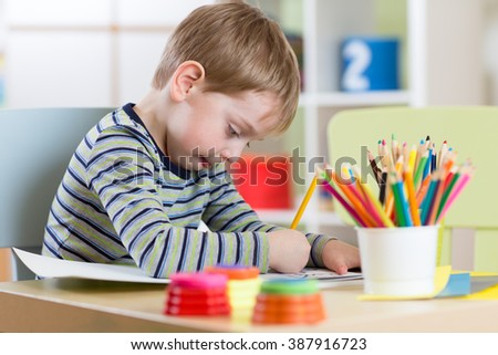 Preschool child use pencils and paints for homework received from kindergarten - stock photo