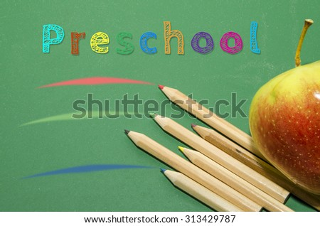 Preschool colorful graphic sign, apples, crayons and blackboard  - stock photo