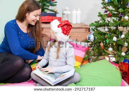 Preschool daughter with mother sitting on the floor next to Christmas tree - stock photo