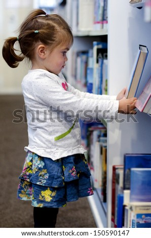 Preschool girl selecting book in library. - stock photo