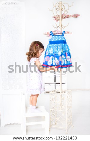 Preschool girl standing on the chair beside coat hanger with a little dress - stock photo