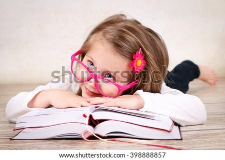 Preschool girl wearing glasses and reading books - stock photo