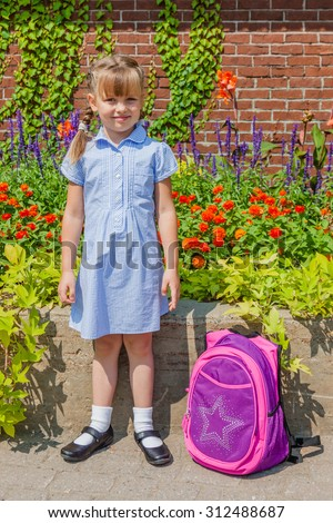 Preschool girl with braids dressed in school uniform gingham blue dress and black classic mary jane shoes standing near the school wall with her backpack. Back to school. - stock photo