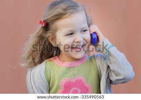 Preschooler blonde girl in having fun during her dialogue by mobile phone - stock photo