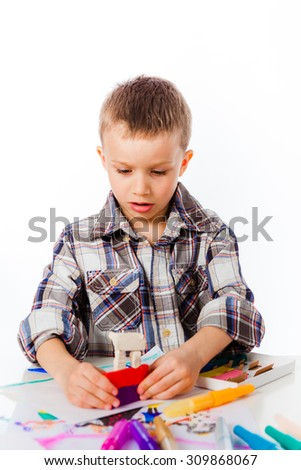 Preschooler boy playing with plasticine sitting by desk - stock photo