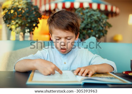 Preschooler boy reading book for elementary school - stock photo