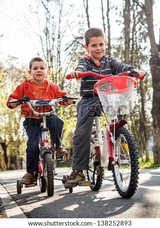 Preschooler boys with bike in park - stock photo