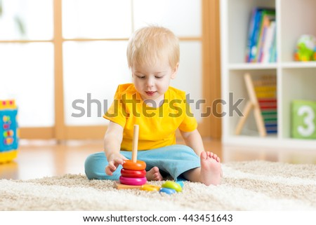 Preschooler child playing with colorful toy. Kid playing with educational wooden toy at kindergarten or daycare center. Toddler boy in nursery room. - stock photo