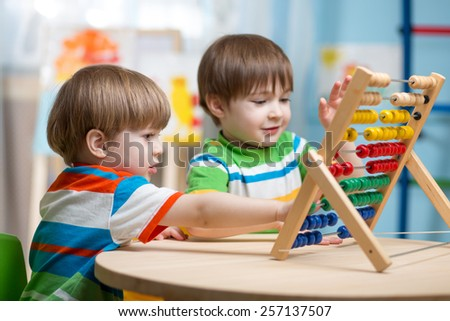 preschooler children boys play with counter toy - stock photo
